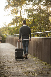 Young man walking with his wheeled luggage on a footbridge - PAF001086