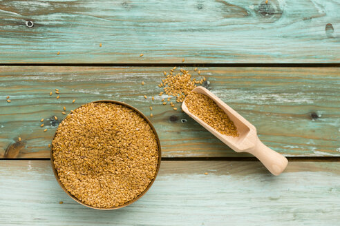 Bowl of golden linseed and shovel on green wood - MYF000694