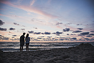 Silhouette of teenage couple standing on beach looking at the sea in front of evening sky - MVC000143