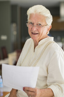Portrait of smiling senior woman with glasses holding sheet of paper - ABAF001574