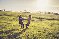 Two little girls turning around together on a meadow in backlight - SARF001006