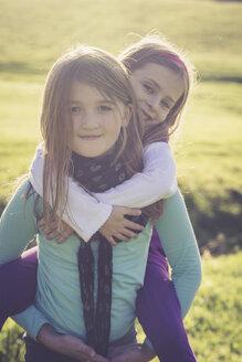 Girl giving another little girl a piggyback - SARF001010