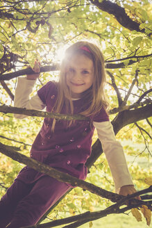 Portrait of smiling little girl climbing in an autumnal tree - SARF001020