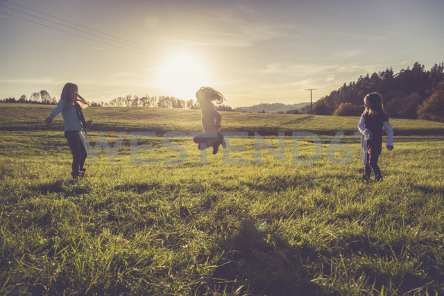 Three little girls playing with a spiral on a meadow in backlight - SARF001015