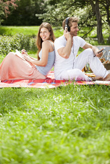 Happy couple on picnic blanket in park - CvK000225