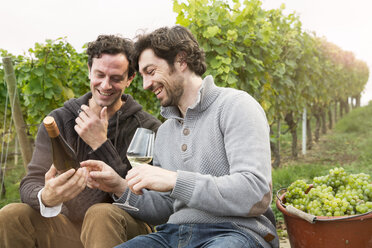 Germany, Bavaria, Volkach, two winegrowers having a break in vineyard - FKF000808