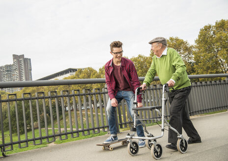 Happy senior man with wheeled walker and adult grandson with skateboard - UUF002648
