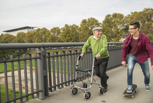 Happy senior man with wheeled walker and adult grandson with skateboard - UUF002651