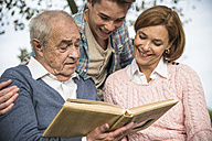 Senior man with grandson and daughter looking at photo album - UUF002668