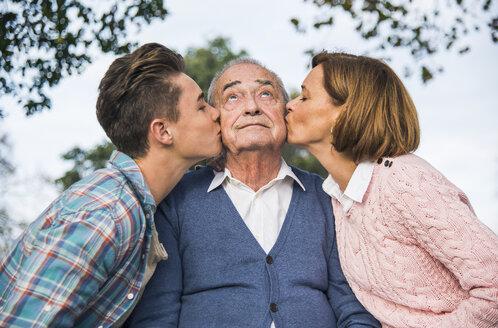 Grandson and daughter kissing senior man's cheek - UUF002672
