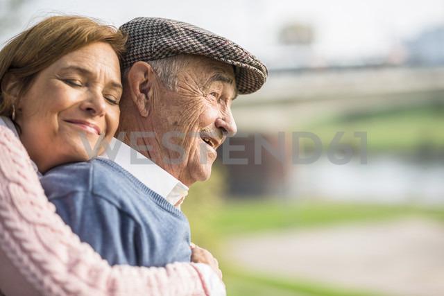 Daughter embracing senior man outdoors - UUF002685