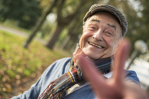 Portrait of happy senior man outdoors doing victory sign - UUF002712