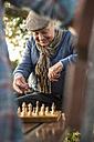 Senior man and grandson playing chess - UUF002722