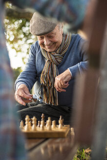 Senior man and grandson playing chess - UUF002722