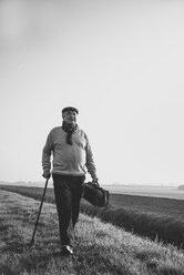 Senior man with bag walking in rural landscape - UUF002697