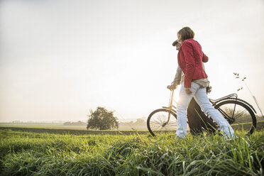 Senior man and daughter in rural landscape with bicycle - UUF002702