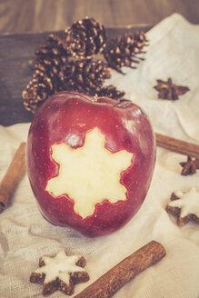 Red apple with star shaped hole, cinnamon stars, cinnamon sticks and fir cones on cloth - SARF001030