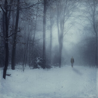 Germany, near Wuppertal, Man walking in snow covered forest, digital manipulation - DWI000287