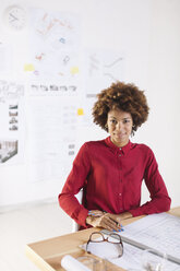 Portrait of smiling young female architect sitting at her desk - EBSF000332