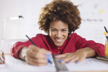 Portrait of laughing young female architect working at her desk - EBSF000336