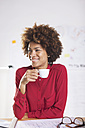 Portrait of smiling young female architect drinking coffee at her desk - EBSF000339