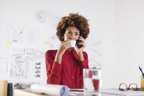 Portrait of young female architect telephoning with smartphone while drinking coffee - EBSF000342