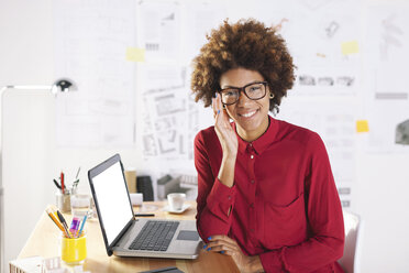 Portrait of smiling young female architect with laptop at her desk - EBSF000352