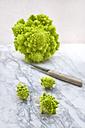 Romanesco, Brassica oleracea convar. botrytis var. botrytis, and kitchen knife on white marble - LVF002214