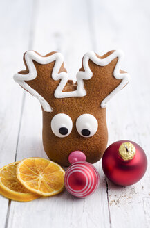 Gingerbread elk, orange slices and christmas baubles on white wood - ODF000866