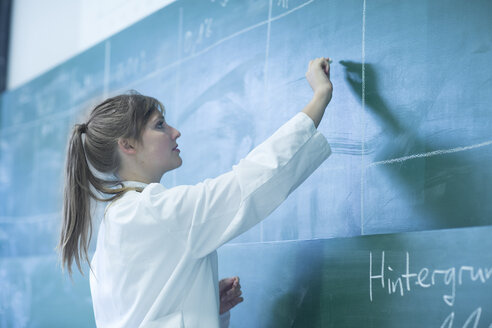 Young female natural scientist writing on blackboard - SGF001046