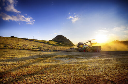 United Kingdom, Scotland, East Lothian, North Berwick, Field, Combine harvester and tractor at sunset - SMA000261