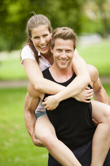 Man carrying smiling young woman piggyback - CvKF000160