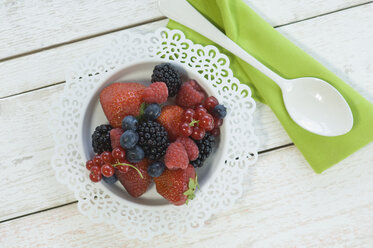 Bowl of different berries, cloth and a spoon on white wood - ASF005493