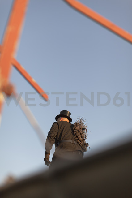 Germany, chimney sweep on rooftop - HCF000082