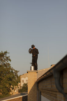 Germany, chimney sweep at work on rooftop - HCF000084