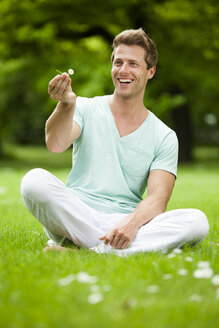 Happy man sitting on meadow in park - CvKF000166