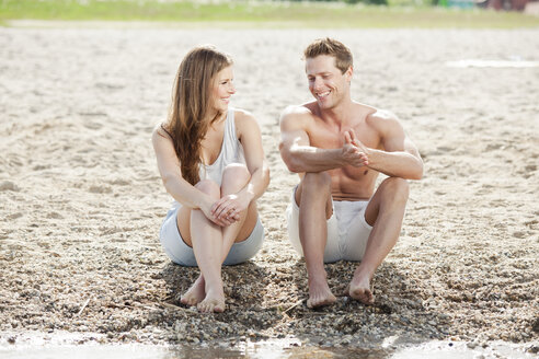 Happy couple sitting on the beach - CvKF000179