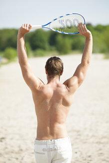 Man with badminton racket on the beach - CvKF000187