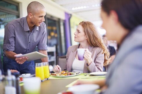 Businessman talking to colleague at dining table - ZEF002211