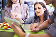Businesswoman showing digital tablet to colleagues at dining table - ZEF002216