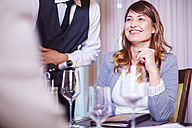 Waiter pouring wine for business associates at hotel restaurant - ZEF002258