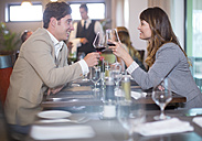 Couple clinking wine glasses in restaurant - ZEF002733