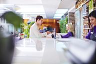 Businessman arriving at hotel reception - ZEF002262