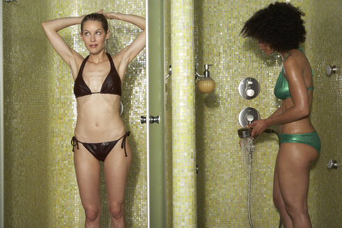 Two women standing in shower cabinets - FSF000390