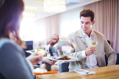 Businessman looking at waiter lifting serving dome in hotel restaurant - ZEF002267
