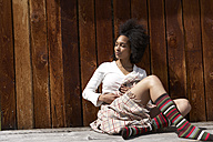 Sunbathing young woman leaning on wooden wall - FSF000365