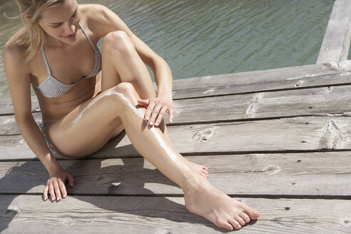 Woman sitting on planks putting on suncream - FSF000369