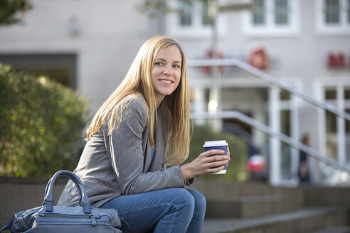 Smiling young women sitting at steps with coffee to go - SHKF000029