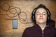 Portrait of teenage boy with closed eyes hearing music with headphones lying on wooden floor - MVC000148