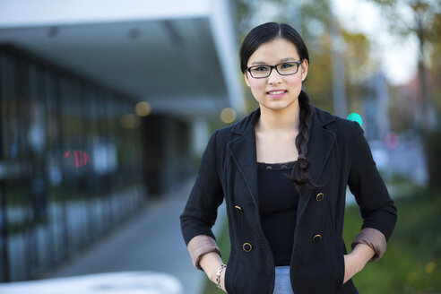 Portrait of smiling young businesswoman wearing glasses - MAD000106